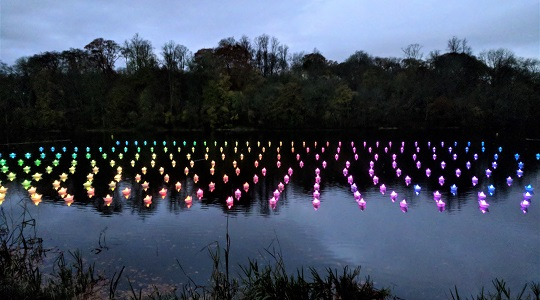 VOYAGE by Aether & Hemera, a  flotilla of colourful origami lit paper boats floating on the water. From London to Oxfordshire